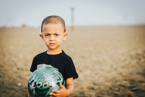 Close-Up Photo of Boy Holding A Ball