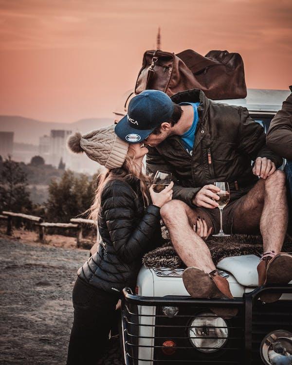 Photo of Couple Kissing While Sitting on Vehicle