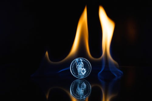Round Silver-colored Coin on Black Surface With Flame