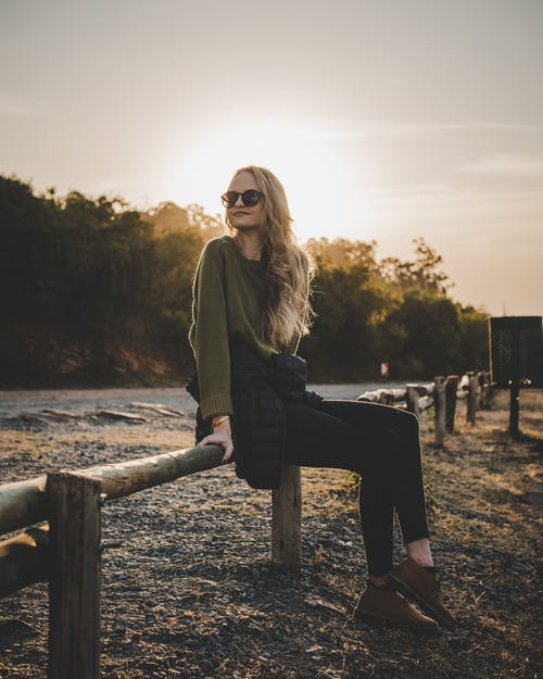 Photo of Woman Sitting on Wooden Railing