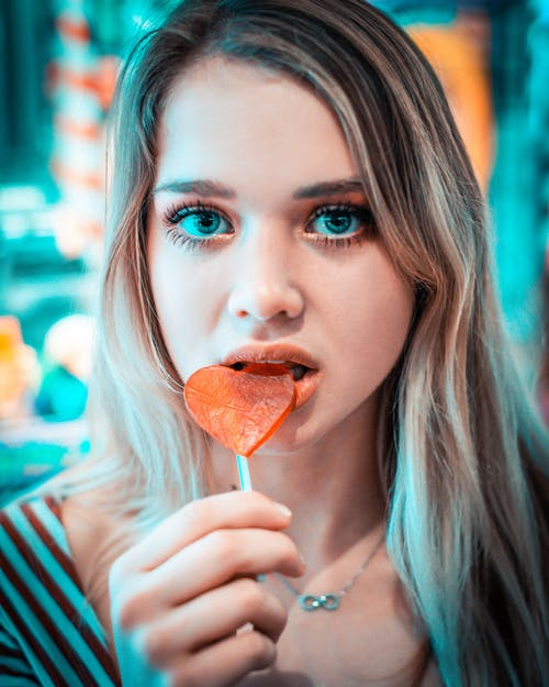 Close-Up Photo of a Woman Eating Lollipop