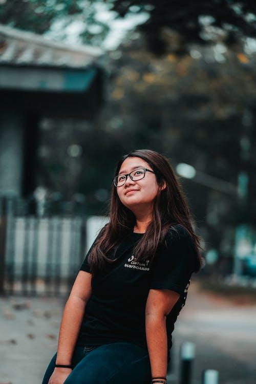 Foto De Enfoque Selectivo De Mujer En Camiseta Negra Sentada Mientras Mira Hacia Arriba