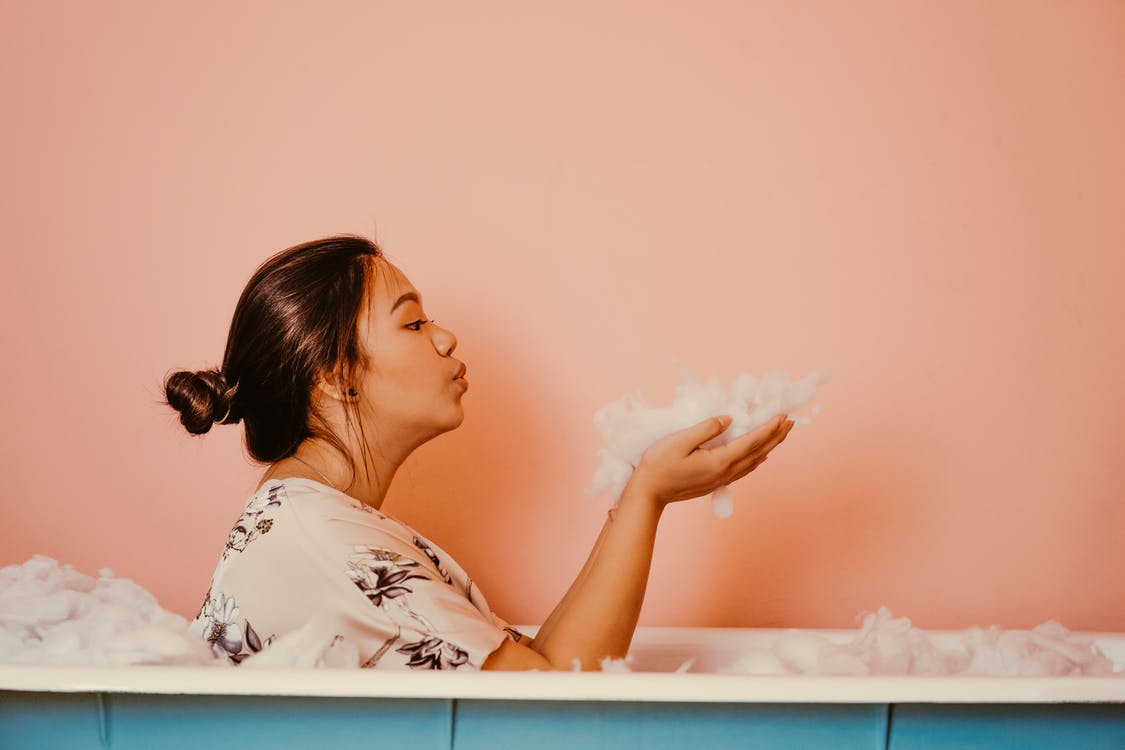 Woman In A Bath Tub Blowing Bubbles