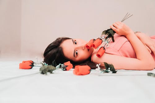 Photo of Woman Lying Down While Holding Red Roses
