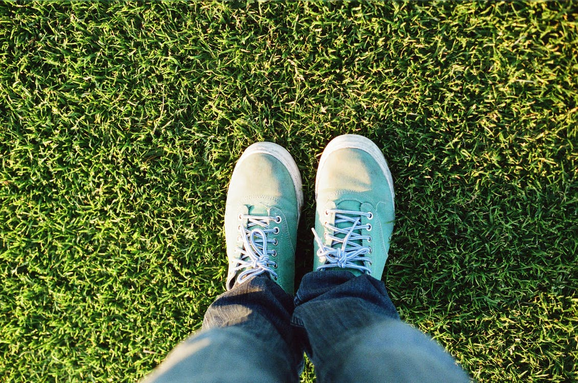 Person Wearing Blue Shoes Standing on Grass