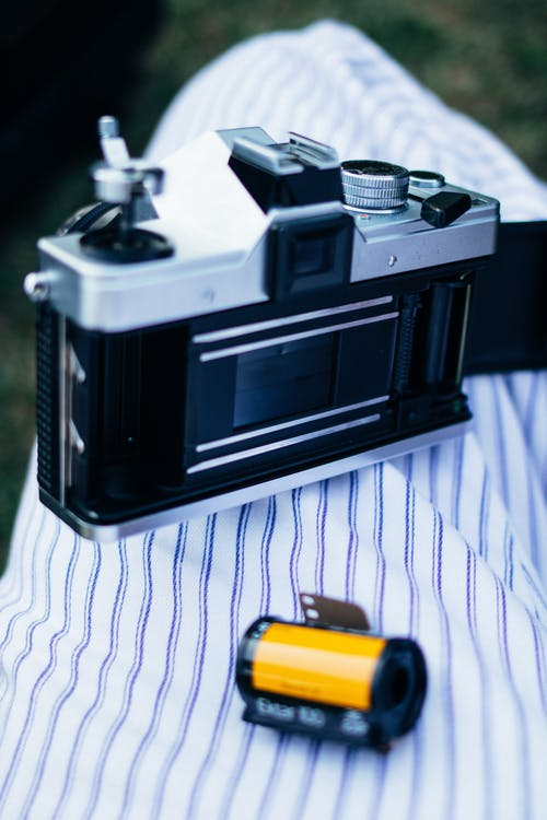 Photograph of a Grey and Black Camera Beside a Roll Film