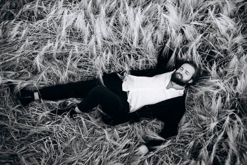 Grayscale Photo of Man Lying on Grass