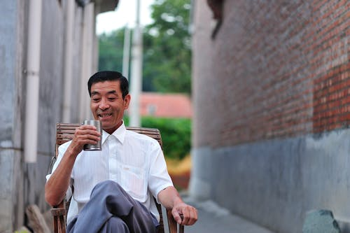 Man Sitting on Wooden Chair Holding a Glass of Drink