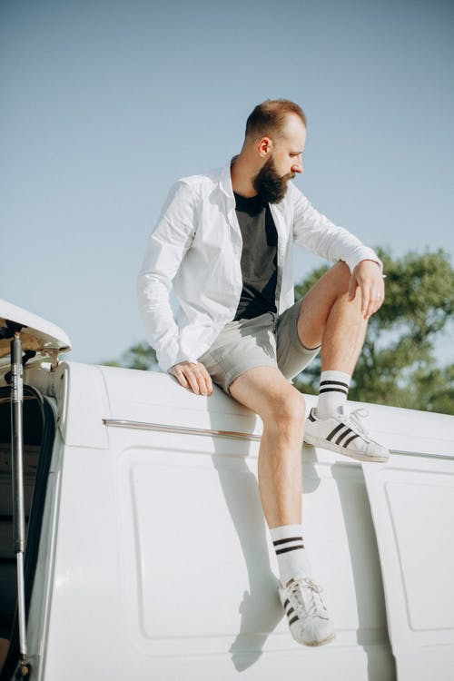 Photo of a Man Sitting on Top of a White Van