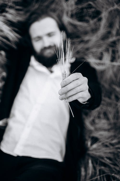 Shallow Focus Photography of a Man Holding Dried Grass