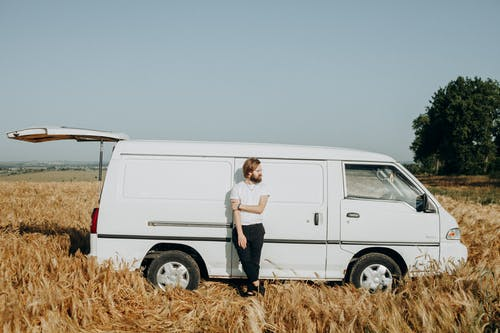 Photo of a Man Leaning on White Van