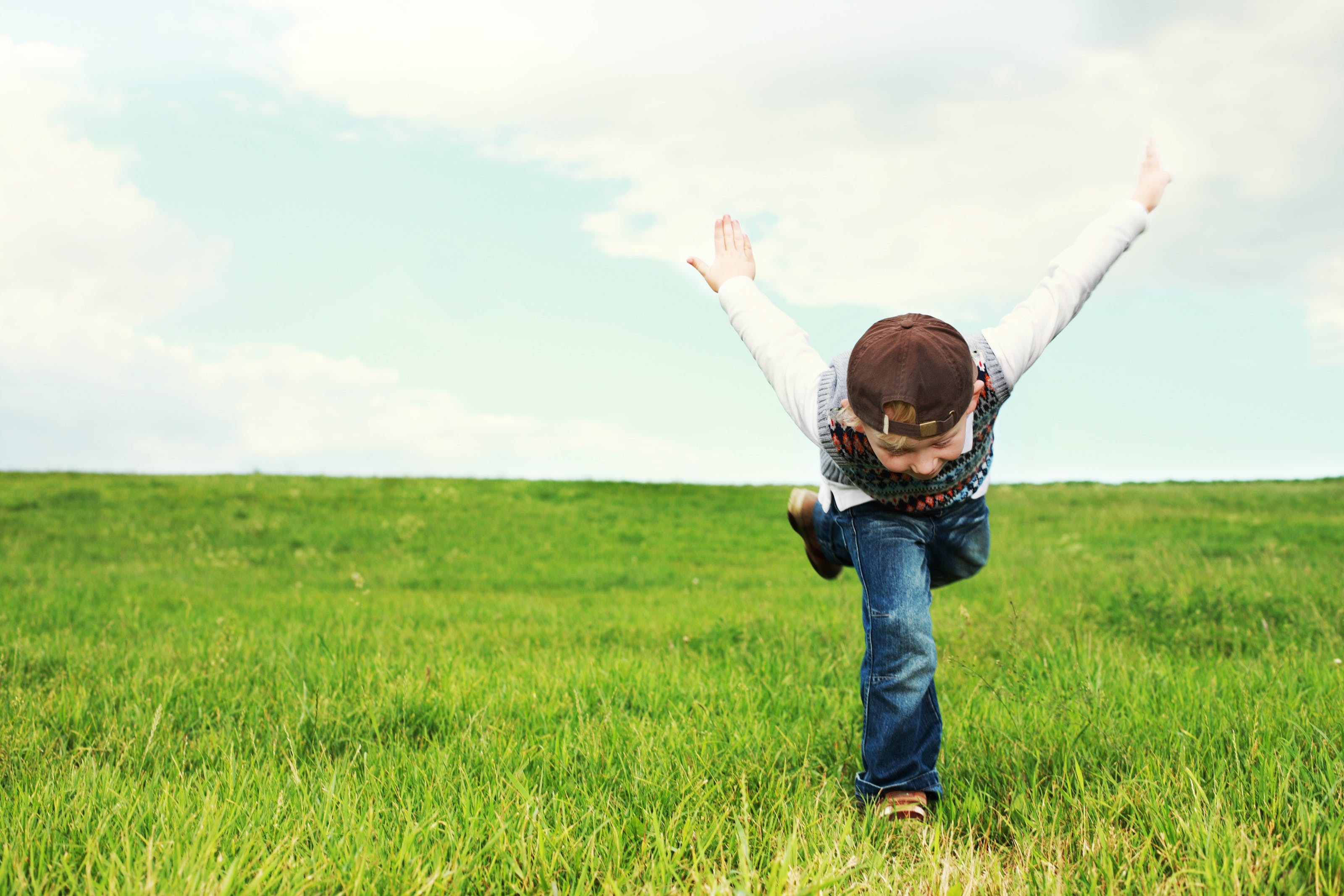 Boy Running on Green Grass Field