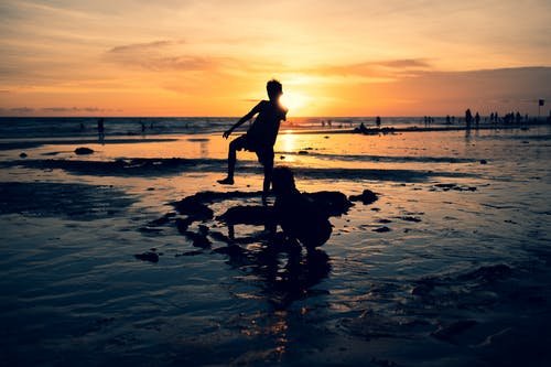 Silhouette Photo of Two Boys on the Seashore