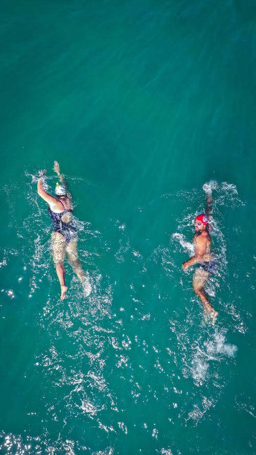Photo of Two People Swimming on Body of Water