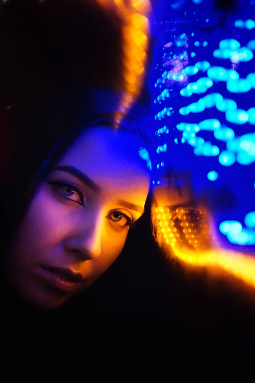 Close-Up Photo of Woman's Face Near Neon Lights