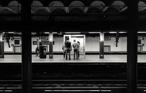 Black and white of anonymous people waiting for train on platform of subway station