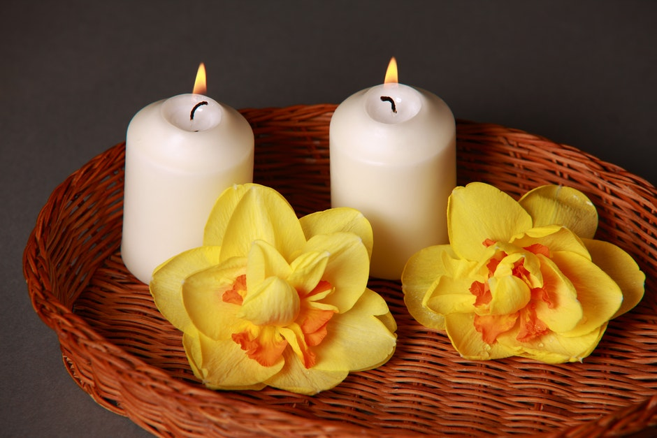 image of an aromatherapy bamboo basket holding two candles and two flowers
