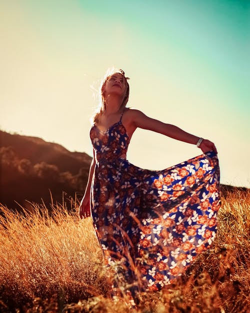 Photo of a Woman in Floral Dress Standing Outdoors