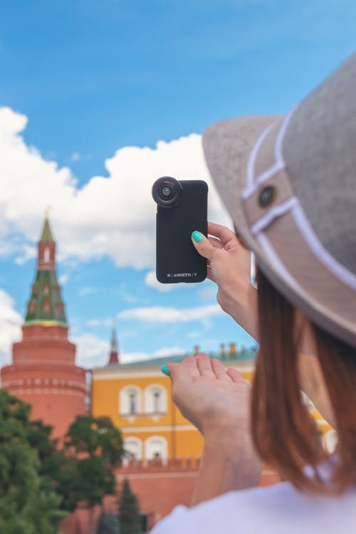 Woman Holding Camera While Pointing It to the Sky