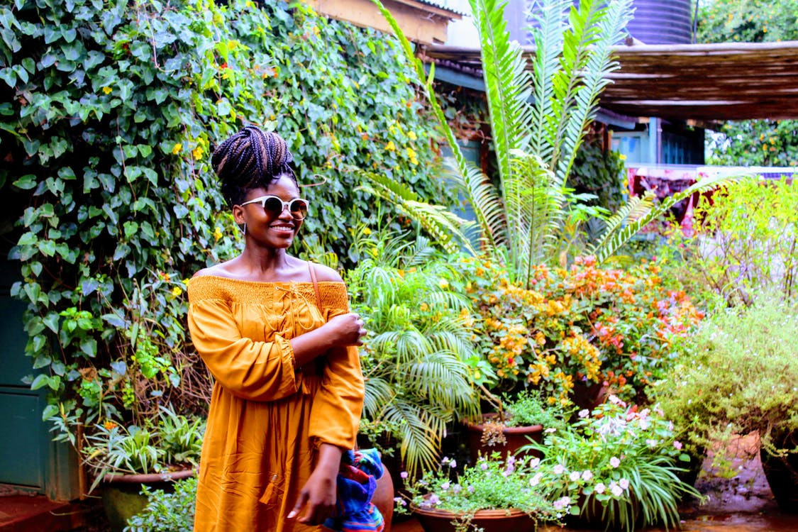Photo of a Woman in Yellow Dress Standing Near Plants