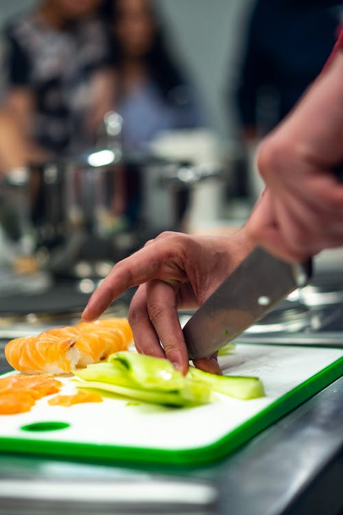 Selective Focus Photo of Person Slicing Vegetable on Chopping Board