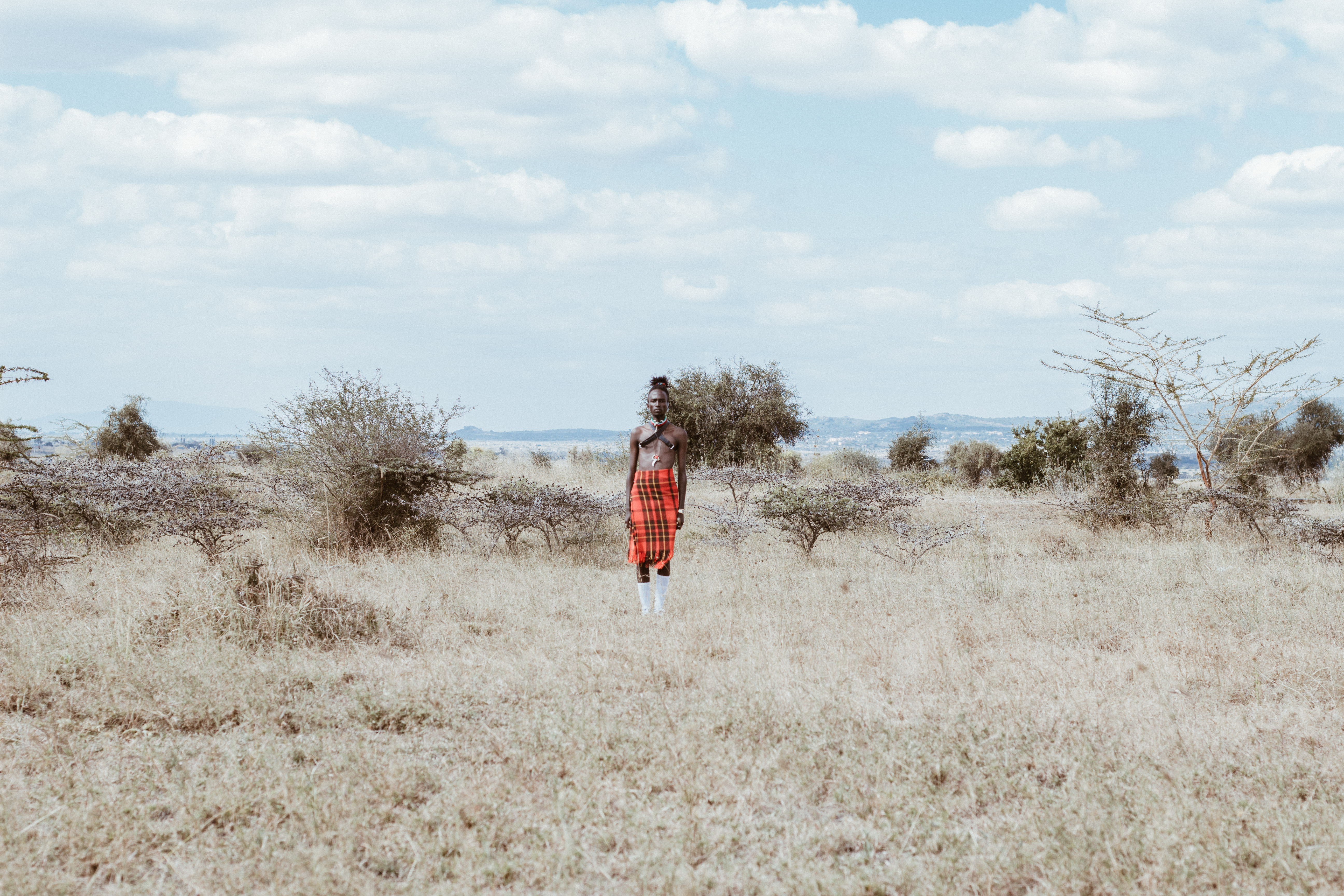 Photo of Man in Red and White Lungi Skirt Standing on Grass Field