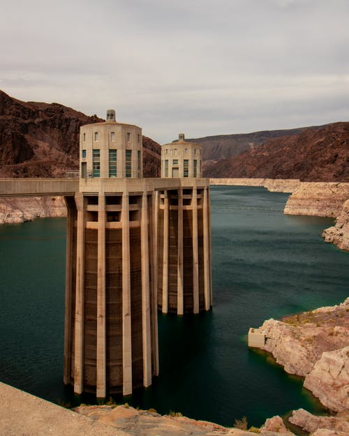 Photo of Concrete Towers on Body of Water