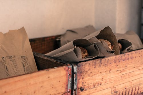Photograph of Food Packaged  in Grey Kraft Paper Bags Placed  in Brown Wooden Open Boxes