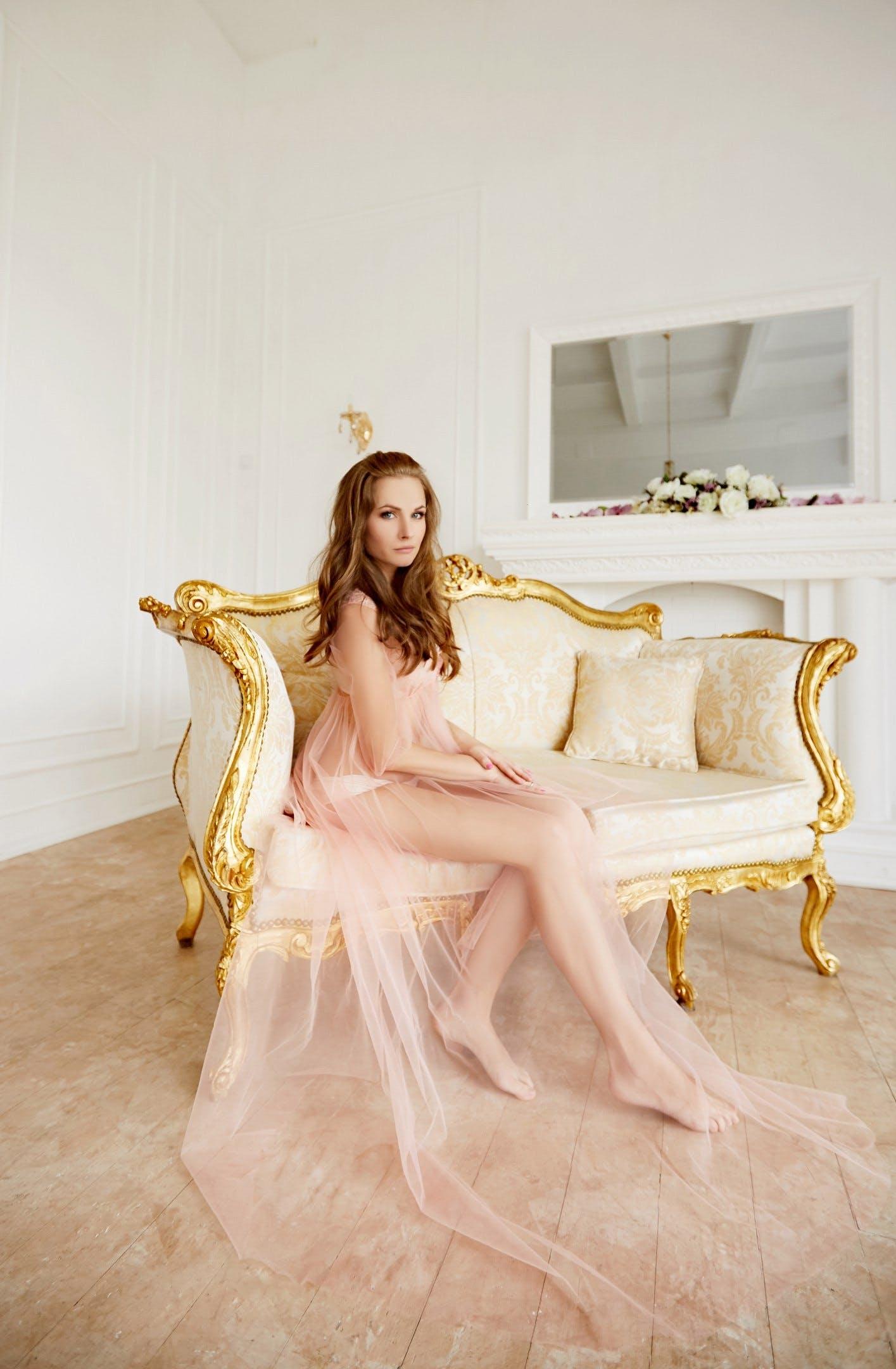 Woman Wearing Lace Dress Sitting on Sofa