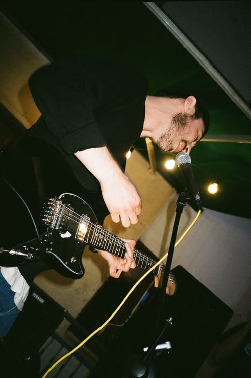 Low-Angle Photo of Man Singing While Playing Electric Guitar