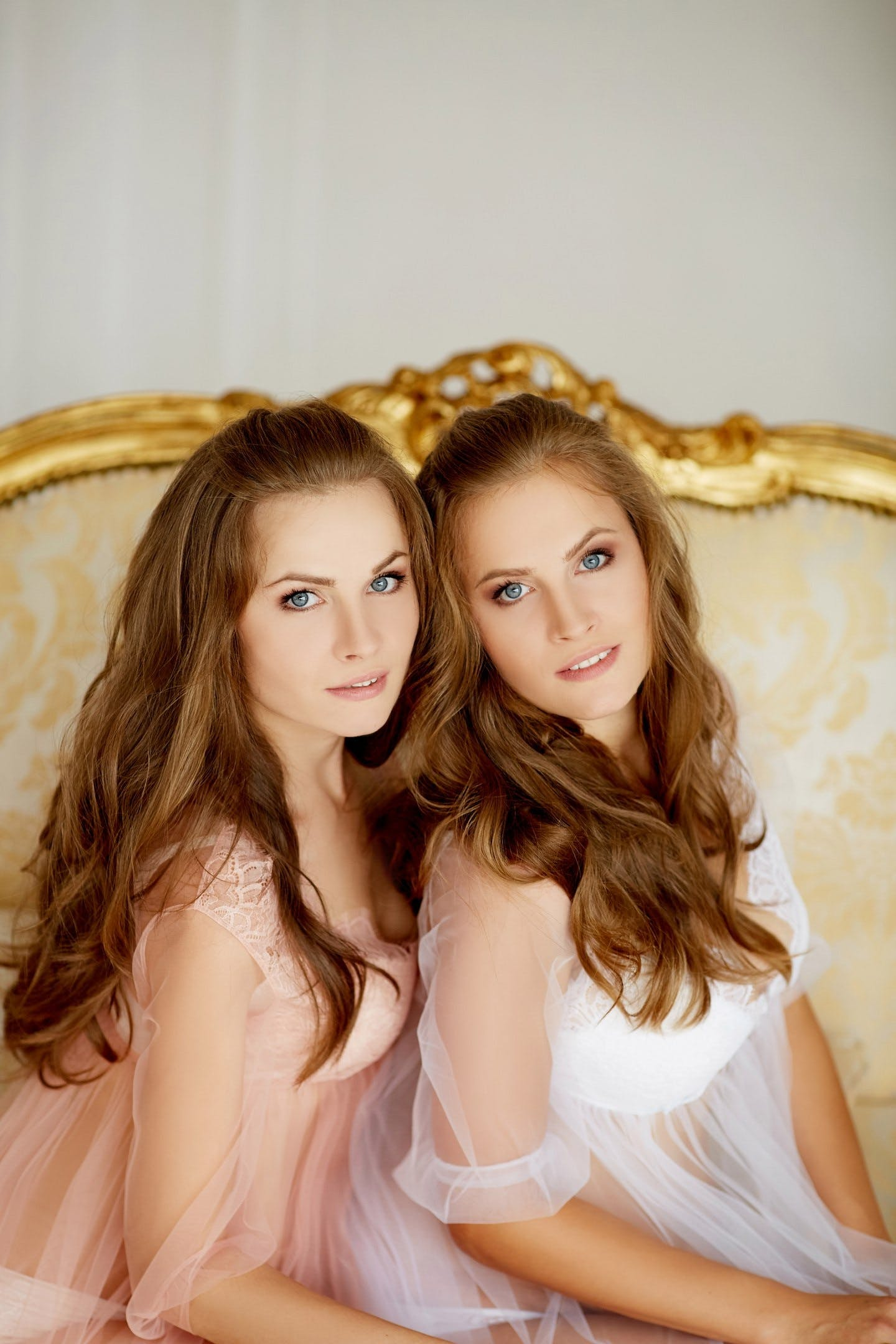 Two Women's Wearing White and Pink Sheer Tops Sitting on Bed