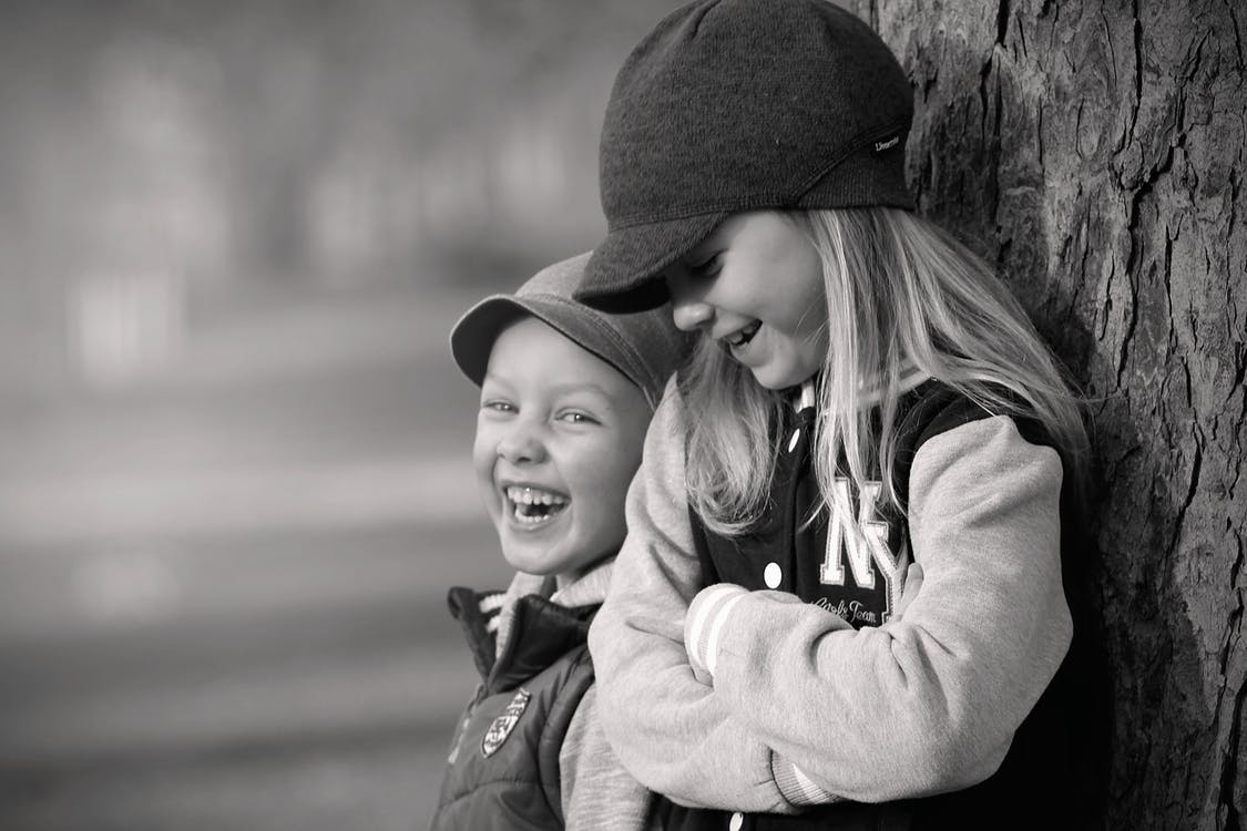Boy and Girl Leaning on Tree