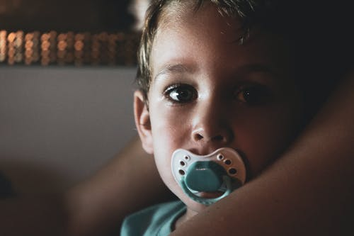 Close-Up Photo of Boy With Pacifier in His Mouth