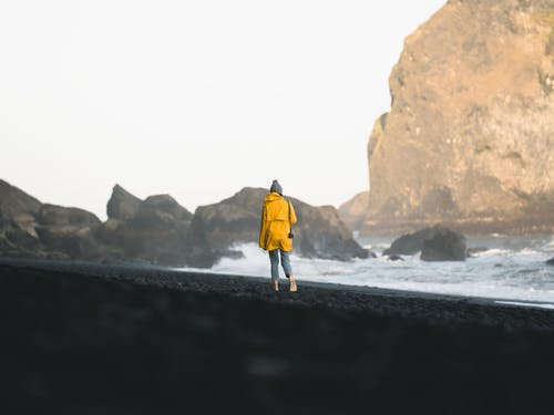 Woman in Yellow Jacket Walking Along Shore