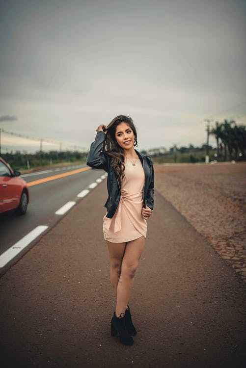 Photo of a Woman in Black Leather Jacket Standing on Road