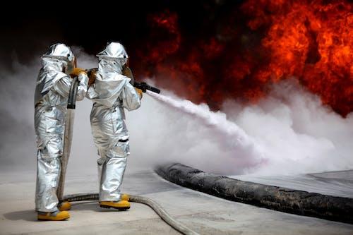 Zwei Feuerwehrleute, Die Mit Dem Feuerwehrschlauch Feuer Fangen