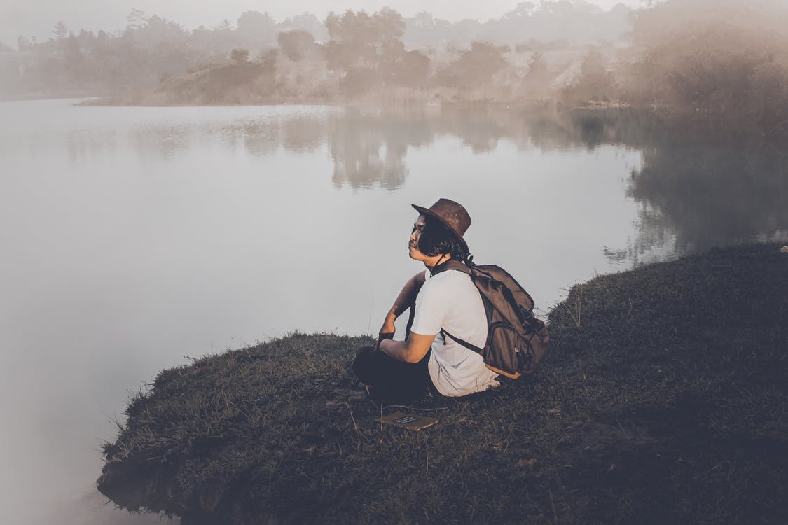 Person Sitting Near Calm Body Of Water