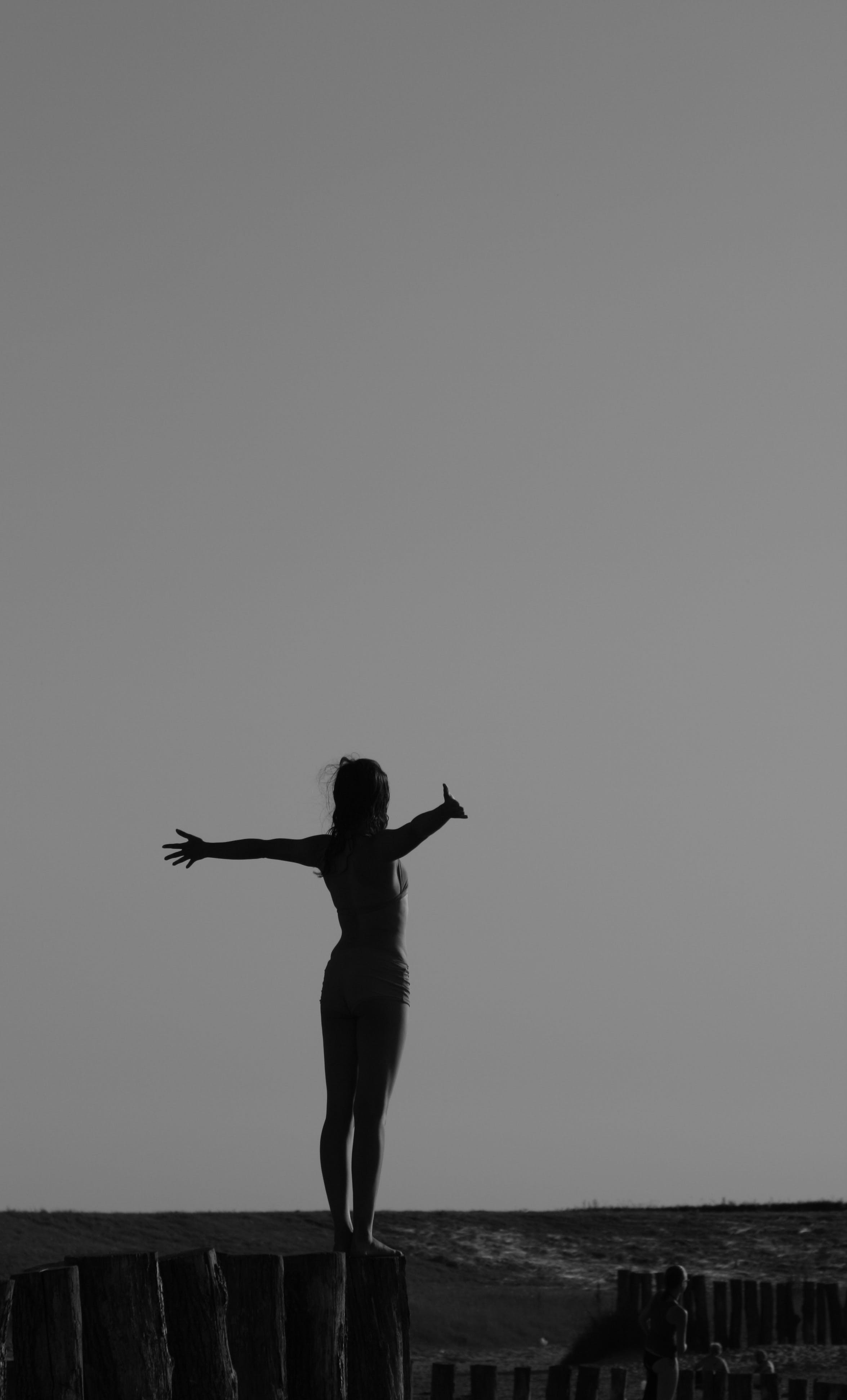 Grayscale Photo of Woman Standing on Log