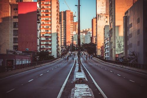 Photo of People Walking on Road Near Buildings