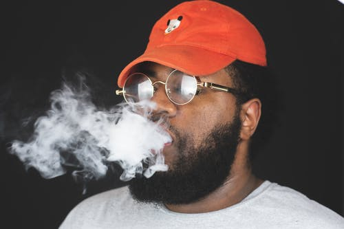 Close-Up Photo of a Man Breathing Smoke