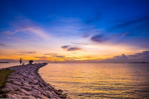 Foto profissional grátis de à beira-mar, água, alvorecer, beira-mar