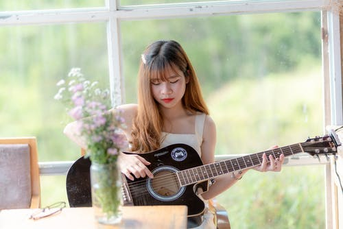 Woman Holding Black Acoustic Guitar