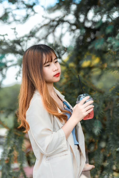 Woman Holding Beverage in Disposable Cup