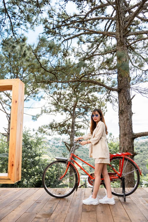 Photo of a Woman Holding a Bike's Handlebars on a Wooden Floor