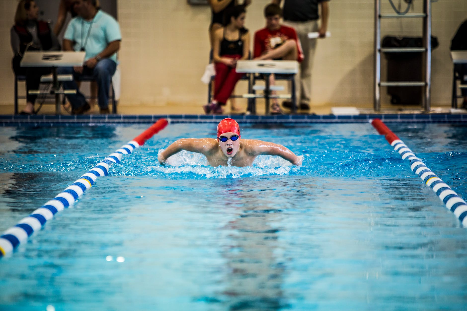 wedstrijdzwemmer doet vlinderslag en zwemt in zwembad