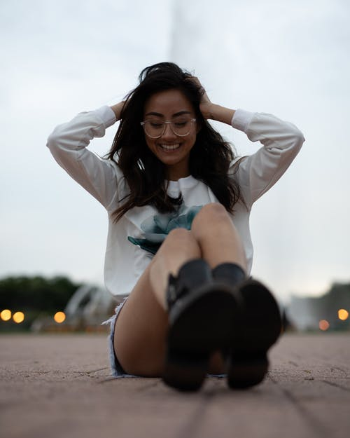 Photo of Smiling Woman in White Sweatshirt and Denim Shorts Sitting on the Ground Posing with Her Hands on Her Head