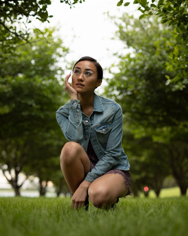Photo of Woman Squat Posing in Park While Looking Up