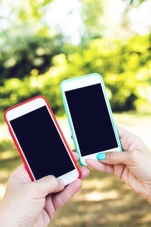 Foto profissional grátis de celulares, dois, foco seletivo, holding