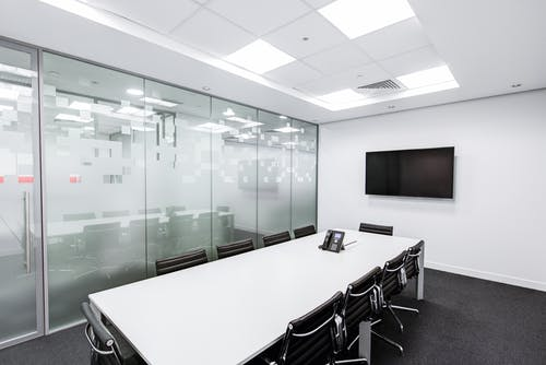 Rectangular White Table With Rolling Chairs Inside Room