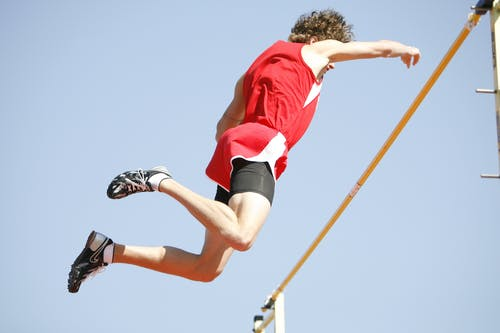 Athlete Jumping over the Rod